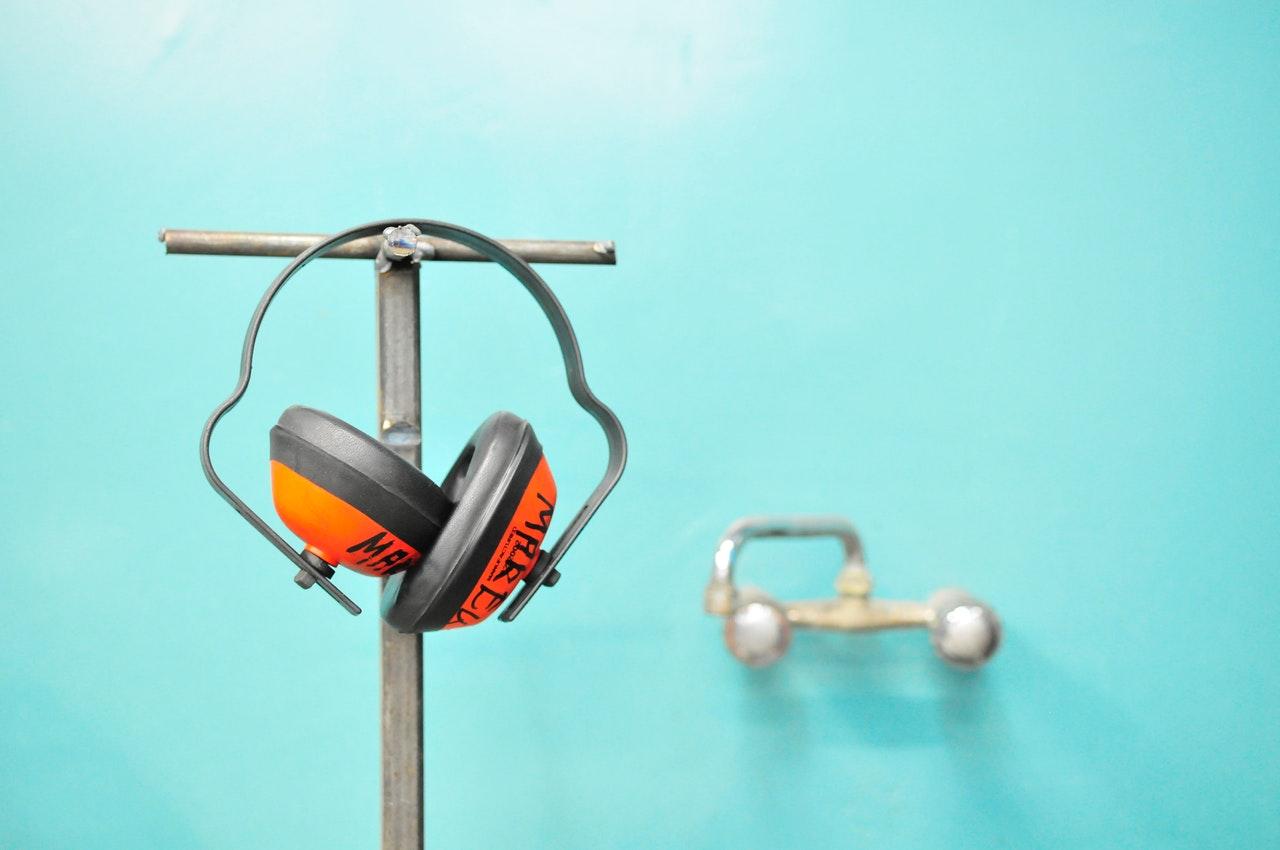 Orange høreværn hænger på stang