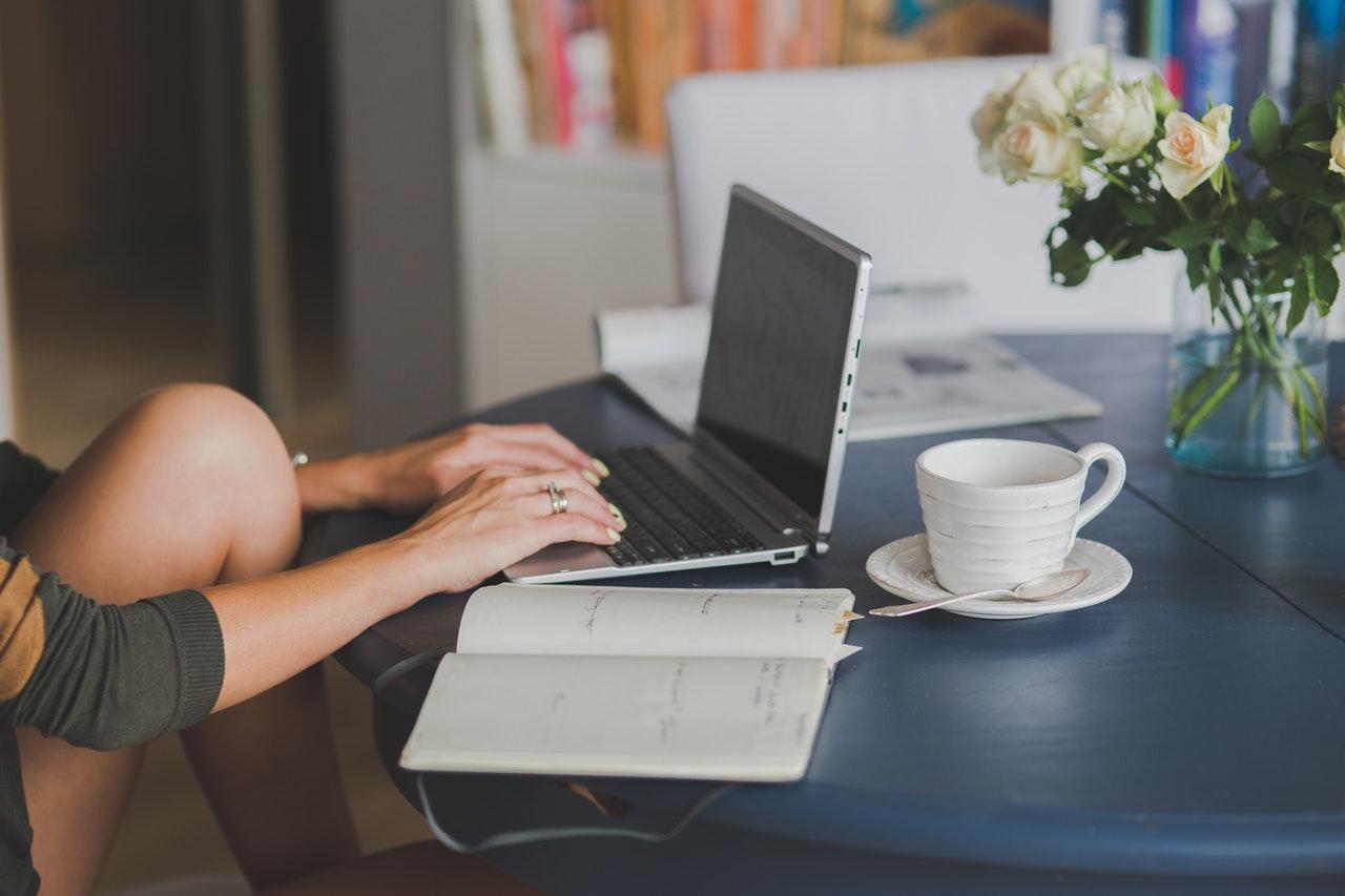 Person bruger computer imens hun drikker kaffe