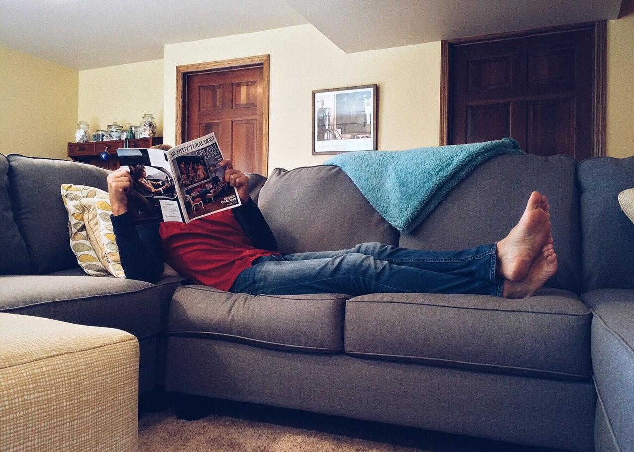 Person ligger på sovesofa med avis